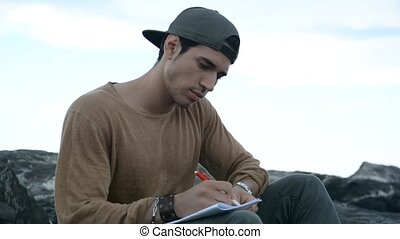 Young Man Writing on Book Sitting at Beach
