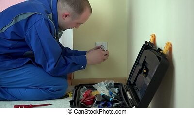 Worker electrician repair wall socket in apartment - Worker...