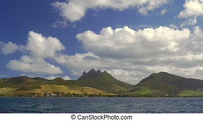 Waterside view of green Mauritius Island with mountains -...