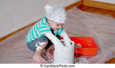 little cute boy kid dunks hands in paint can painting wall...
