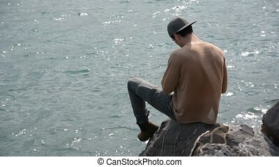Young Man Sitting and Thinking in front of Sea - Shirtless...