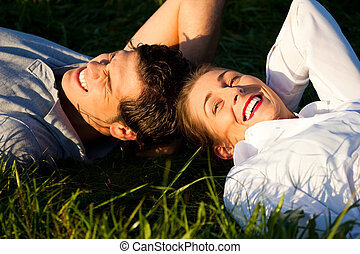 Couple lying on meadow in the sunshine