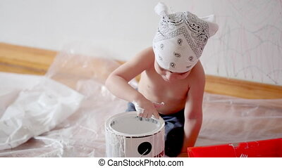 little cute boy kid dunks finger in paint can painting wall...