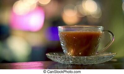 Hot milk tea in cafe - Hot milk tea in a glass cup in a cafe