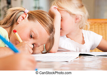 Children doing homework for school together helping each...