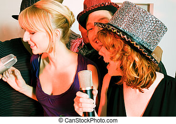 Group of friends having a karaoke party - People having a...
