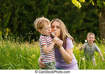 Family summer - blowing dandelion seeds
