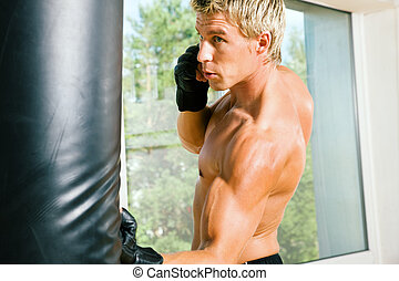 Martial Arts Punch - Boxer hitting the sandbag hard