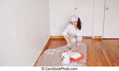 Beautiful girl makes repairs dunks roller on paint
