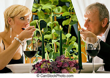 Mature couple eating romantic dinner in a fancy restaurant -...