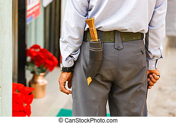 Gurkha officer with gurkha knife attached to the back of his...