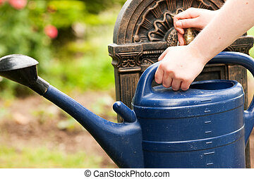 Refilling the watering pot - Garden scene - woman, only...