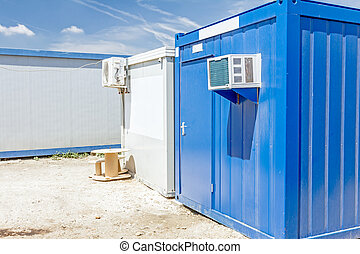 Air compressor is set on the outside wall of container office