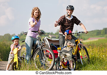 Family riding bicycles in summer - Family with two children...