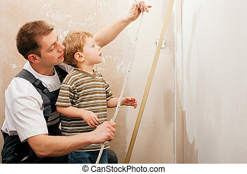 Father and son measuring dry wall - Father and son measuring...