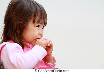 Japanese girl eating rice cracker (2 years old)