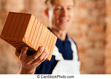 bricklayer with brick on construction site