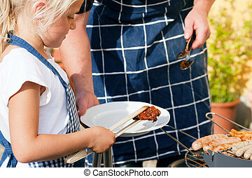Dad and kid doing the BBQ - Father and daughter preparing...