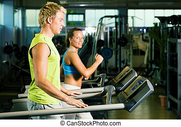 Couple on treadmill in gym