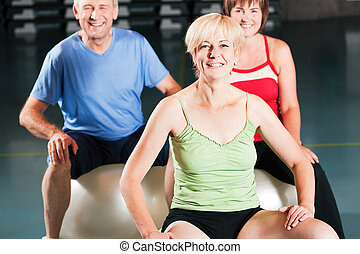 People in gym on exercise ball - Three people - mature and...