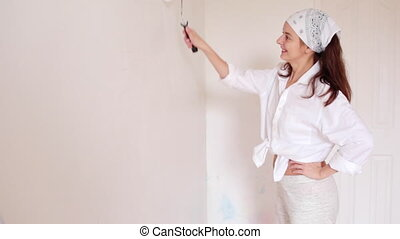 the young woman is painting the room in white color and smiling