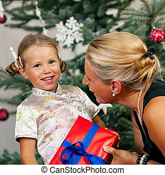 Christmas - child receiving a gift - Young girl receives a...