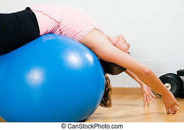 Woman and fitness ball - Woman on top of a blue fitness ball...