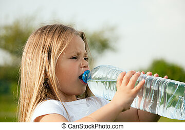Kid drinking bottled water - Kid drinking water from a...