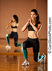 Beautiful fit woman works out in a fitness gym making lunge...