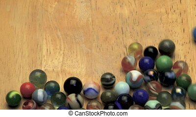 Rolling marbles on wooden board