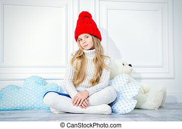 Cute little girl wearing knitted winter clothes posing with her teddy bear.