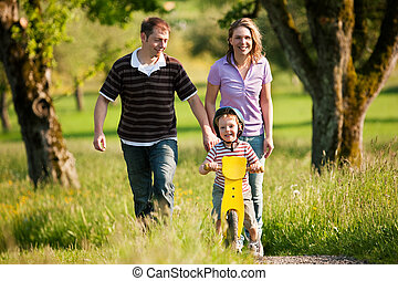 Family having a walk outdoors in summer, their little son...