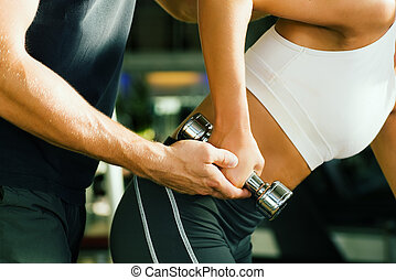 Assistance by the trainer - Young woman lifting a dumbbell...