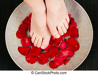Feet wellness - Feet in above a bowl with water and rose...
