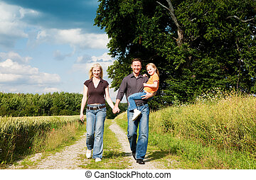 Family having a walk carrying child