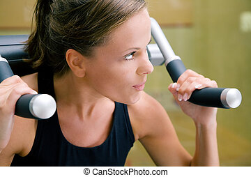 Woman working out in gym - Woman working out lifting weights...