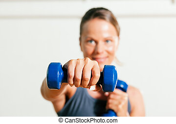 Woman with dumbbell in gym