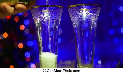 Sparkling wine is poured into glasses. In the background, bokeh lights and garlands of Christmas fir
