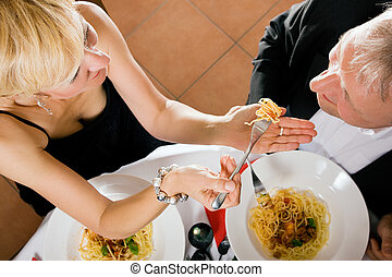Couple eating pasta for dinner - Romantic mature couple...