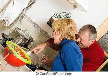 Senior couple cooking dishes in kitchen