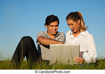 Couple with laptop on meadow