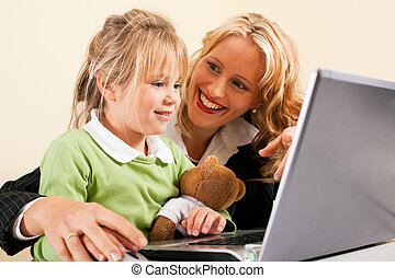 Businesswoman and mother showing kid the internet - Family...