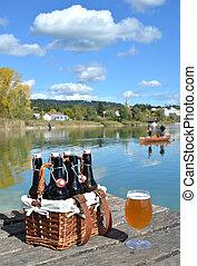 Beer bottles in the vintage basket on a wooden pier