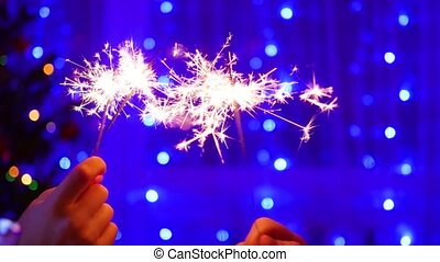 sparklers lit at the party. In the background, bokeh lights and garlands of Christmas fir