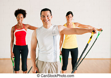 Gymnastics training in gym - Group of three people in...