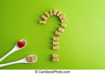 Brown sugar cubes shaped as a question mark over greenery...
