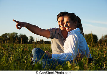 Couple on meadow in sunset
