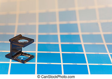 Magnifier or printer's loupe sits on a cyan test sheet in a...