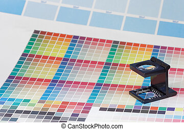 Magnifier or printer's loupe sits on a colorful CMYK test...
