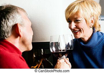 Senior couple drinking red wine - Mature couple having fun...